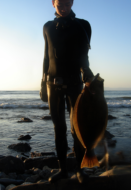 A man in a wetsuit stands on a rocky shore holding a small halibut