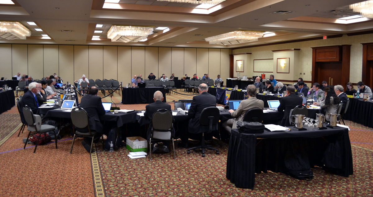 At a Council meeting, a group of people in professional dress sit around a u-shaped table in a hotel ballroom