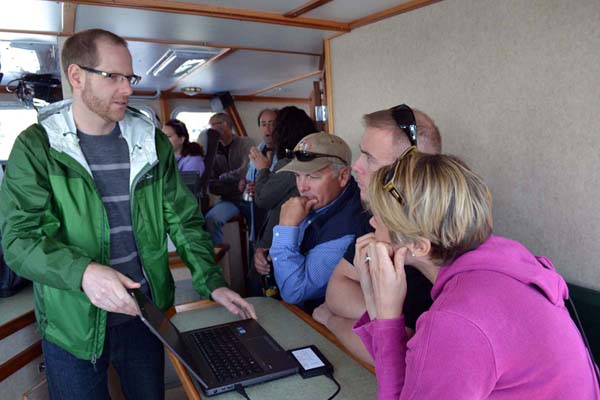 Members of the Council staff gather around a computer screen to learn about electronic monitoring.