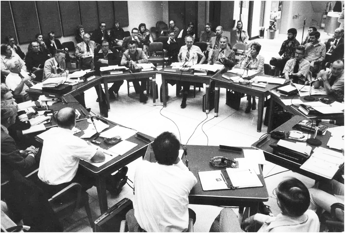 About 20 men and one woman sit around a table in the 1970s